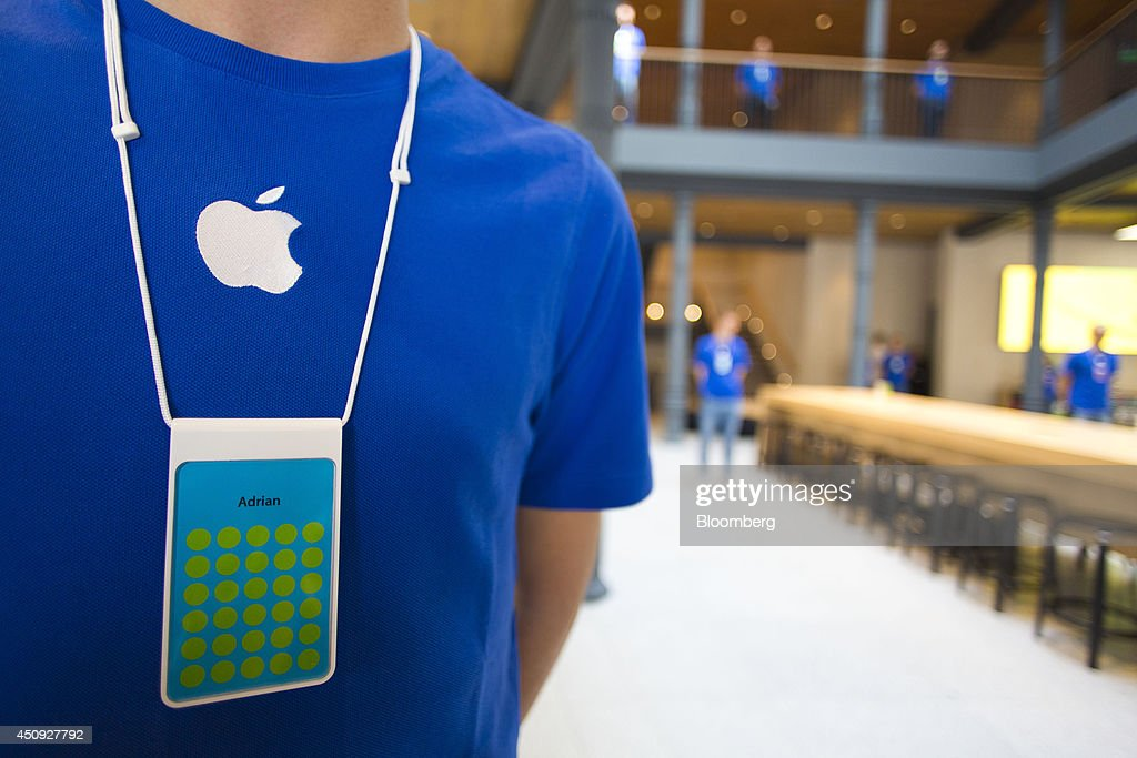 an employee wears a blue apple branded t shirt and name badge during