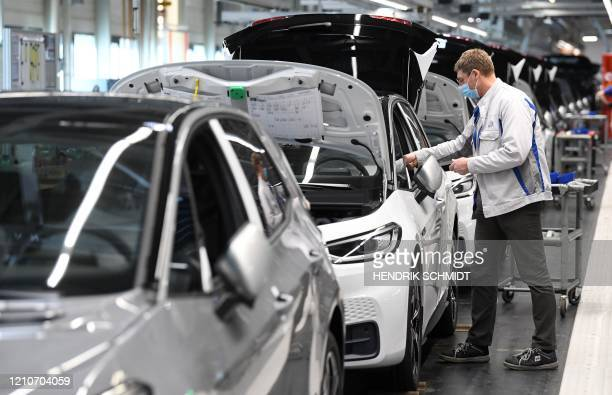 An employee wears a face mask as he works on the assembling of a Volkswagen ID.3 electric car at the plant of German car maker Volkswagen in Zwickau,...