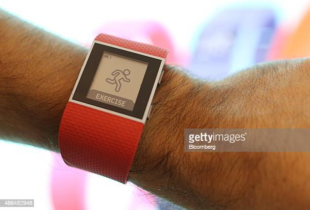 An employee wears a Fitbit Inc Surge smartwatch during the IFA International Consumer Electronics Show in Berlin Germany on Friday Sept 4 2015 IFA is...