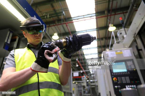 An employee wears a pair of Hololens 3D glasses while holding gear wheels for an automatic automobile transmission system during an Industry 40...