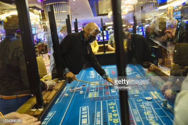 An employee wears a protective mask and face shield while overseeing the blackjack table at the Hard Rock Hotel and Casino in Atlantic City, New...