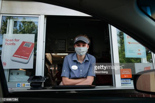 An employee wears a protective mask while working the drive thru window of a Chick-fil-A Inc. Restaurant in Bentonville, Arkansas, U.S., on Thursday,...
