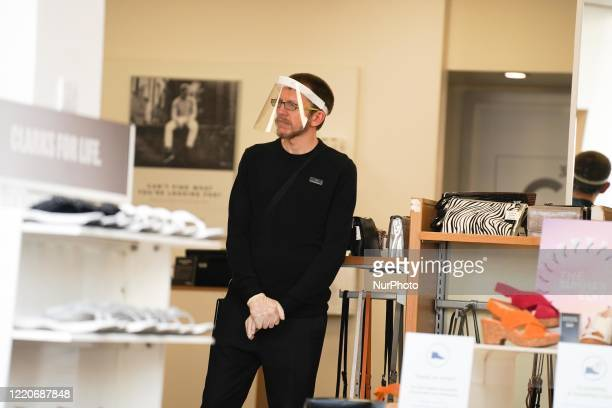 An employee wears a protective visor at Clarks shoe shop in Sheffield, England on 17 June 2020.