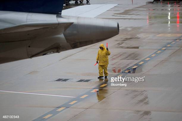 An employee wears a rain suit while signaling a plane out of the gate at Ronald Reagan National Airport in Washington DC US on Tuesday Nov 26 2013...