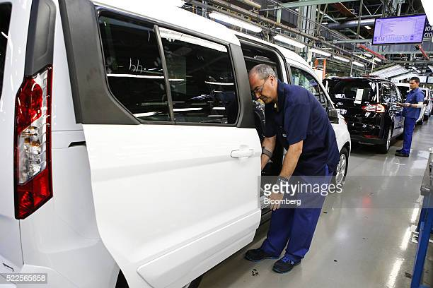 An employee wears a Samsung Electronics Co smartphone on his arm to assist with final quality control checks on completed automobiles at the end of...
