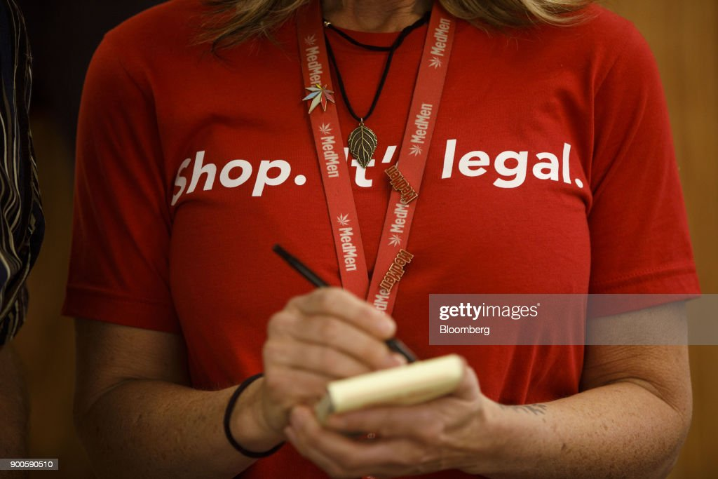 An employee wears a shirt reading 'Shop. It's Legal.' while taking an order for a customer at the MedMen dispensary in West Hollywood, California, U.S., on Tuesday, Jan. 2, 2018. California launched legal marijuana Monday, and customers lined up to celebrate the historic moment in San Diego, Sacramento and Oakland -- some of the municipalities given the green light to start sales on January 1. Meantime, in Los Angeles and San Francisco, the state's first- and fourth-largest cities, customers were turned away empty handed.Photographer: Patrick T. Fallon/Bloomberg via Getty Images
