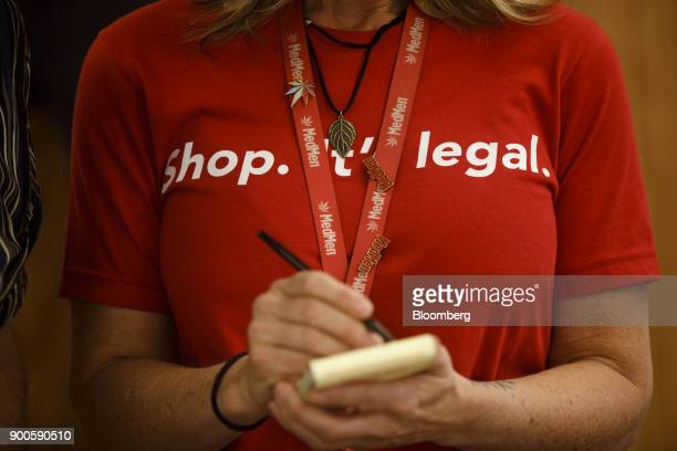 An employee wears a shirt reading 'Shop It's Legal' while taking an order for a customer at the MedMen dispensary in West Hollywood California US on...