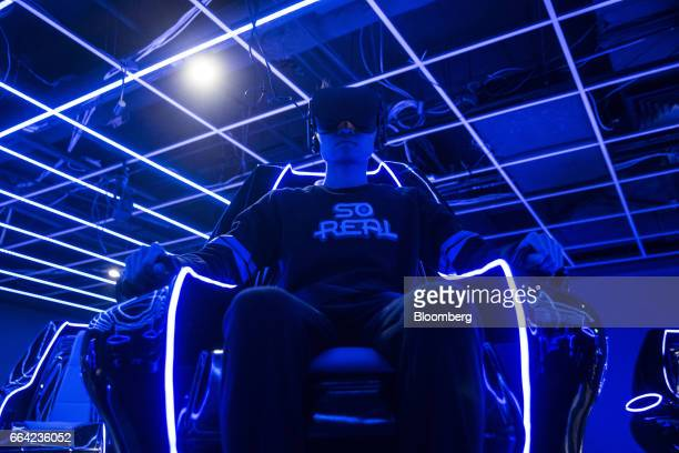 An employee wears a virtual reality headset while demonstrating a 4D cinema that can accommodate 23 people at the SoReal virtual reality park in...