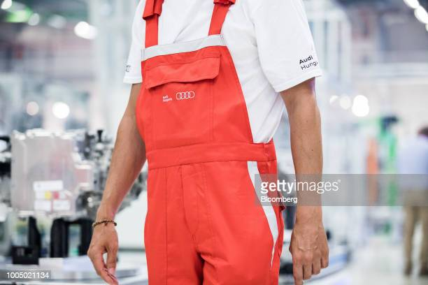 An employee wears branded red overalls inside the Audi AG production plant in Gyor Hungary on Tuesday July 24 2018 Germany's carmakers are fighting...