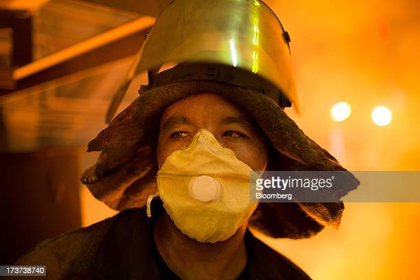 An employee wears heat protective clothing while working in the blast furnace at OAO Mechel's metallurgical plant in Chelyabinsk Russia on Wednesday...