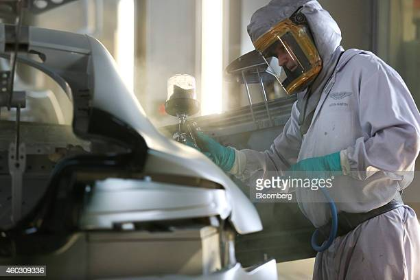 An employee wears protective clothing and a mask as he sprays paint onto the bodywork of an Aston Martin V8 Vantage automobile in the paintshop at...