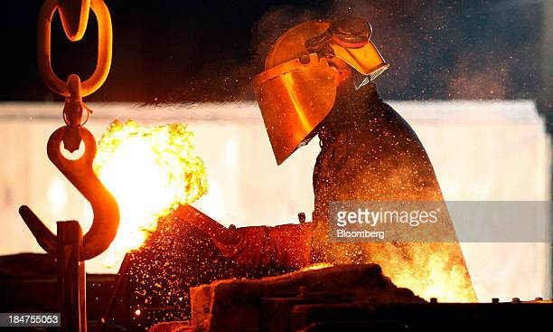 An employee wears protective clothing as he removes slag from molten spheroidal graphite iron in the foundry at Specialised Castings Ltd in Denny UK...