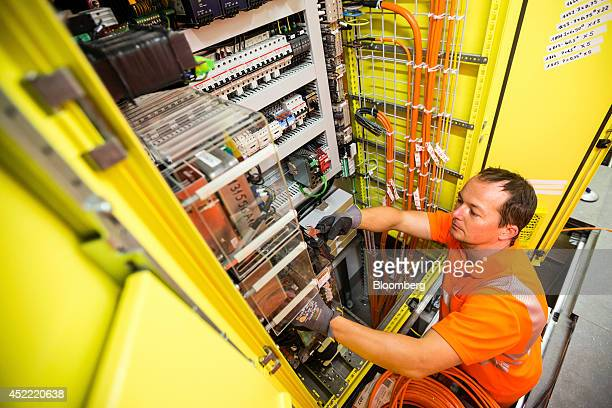 An employee wears safety clothing as he works to install electricity connections in an access tunnel to the Gotthard Base Tunnel in Faido Switzerland...