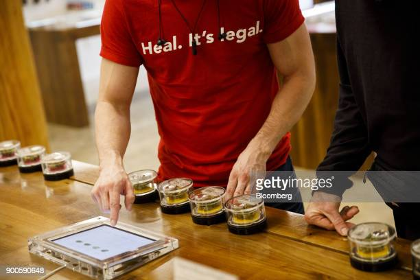 An employee wears shirt reading Heal It's Legal while helping a customer select marijuana strains at the MedMen dispensary in West Hollywood...