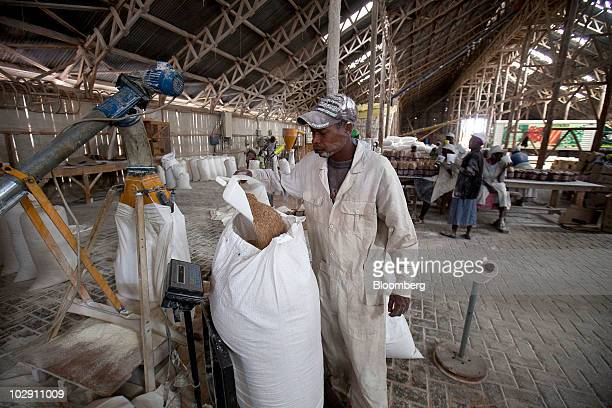 An employee weighs a sack of wheat at a mill in Narok Kenya on Friday July 9 2010 Three years of inadequate rainfall in Kenya triggered the country's...