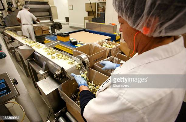 An employee weighs and packs boxes of butterscotch lollipops at the See's Candies Inc lollipop factory in Burlingame California US on Thursday Dec 8...