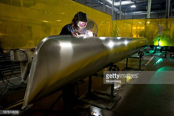 An employee welds a beed onto the nose of an aluminum pontoon during the fabrication process at the Nautic Global Group production facility in...