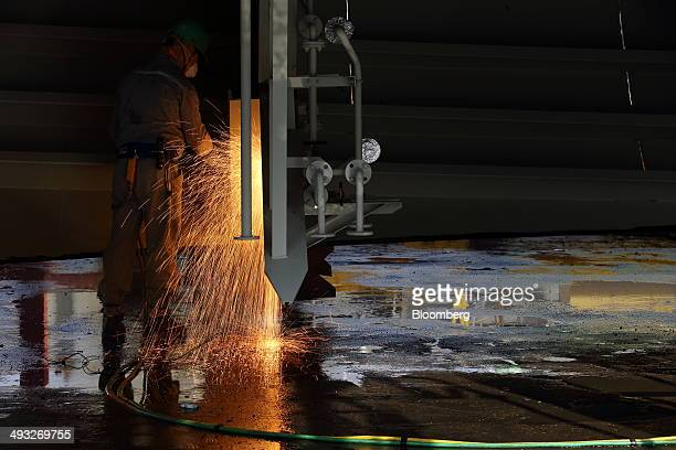 An employee welds a component of a ship under construction at the Hyundai Mipo Dockyard Co shipyard an affiliate of Hyundai Heavy Industries Co in...