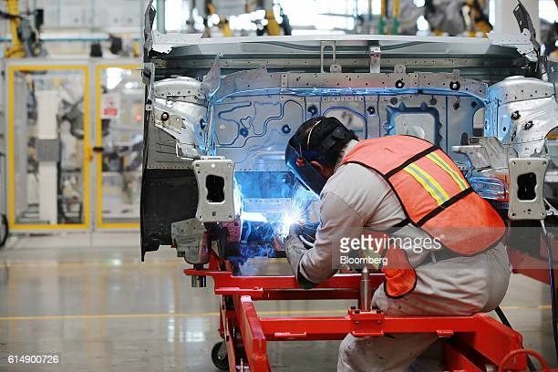 An employee welds a test chassis for a Volkswagen AG Tiguan compact sport utility vehicle at the company's new production plant in Puebla Mexico on...