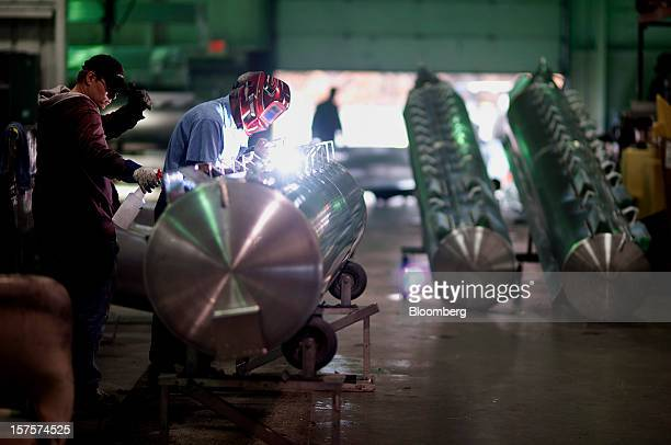 An employee welds mounting brackets to an aluminum pontoon during the fabrication process at the Nautic Global Group production facility in Elkhart...
