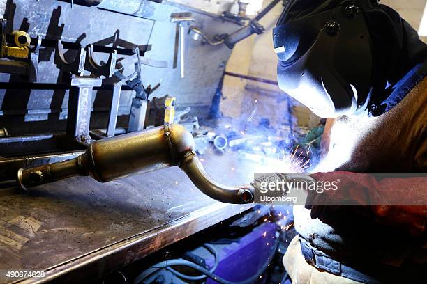 An employee welds parts on to a automobile catalytic converter emission control device at BM Catalysts in Mansfield UK on Wednesday Sept 30 2015...