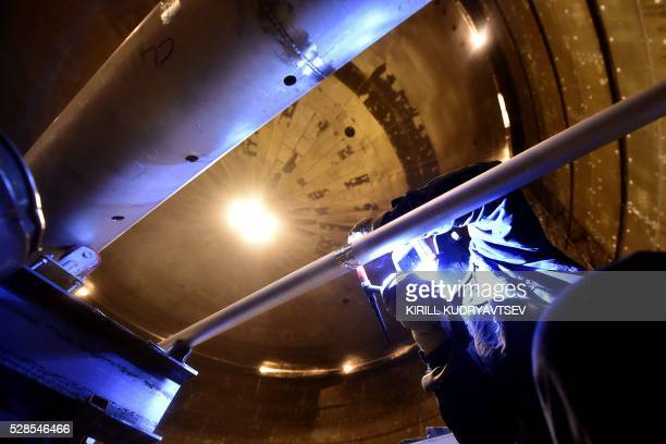 An employee welds pipes inside a natural gas reservoir under construction at the port of Sabetta in the Kara Sea shore line on the Yamal Peninsula in...