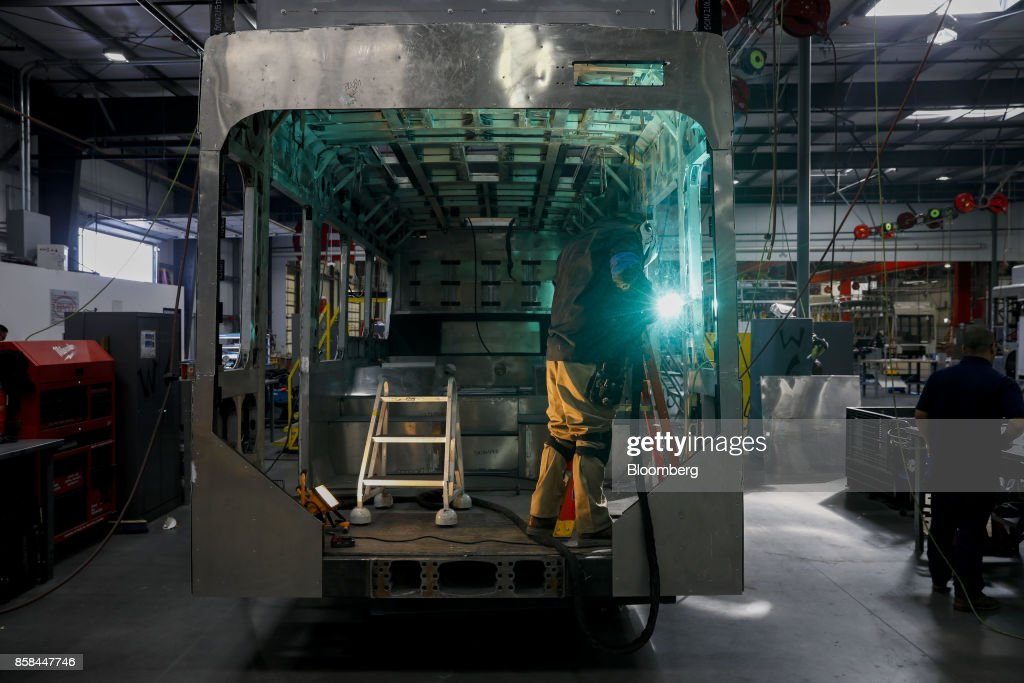 An employee welds the frame of an electric vehicle at the