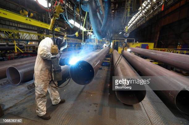 An employee welds the joint on a steel pipe at the SAW Pipe Mills operated by Liberty Commodities Ltd in Hartlepool UK on Thursday June 14 2018 UK...