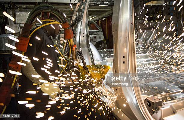 An employee welds together a frame for a sports utility vehicle during production at the General Motors Co assembly plant in Arlington Texas US on...