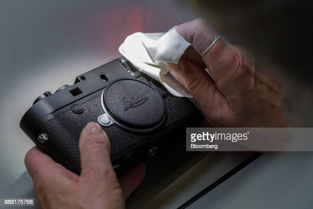 An employee wipes clean a Leica M10 rangefinder digital camera during final quality checks at the Leica Camera AG factory in Wetzlar Germany on...