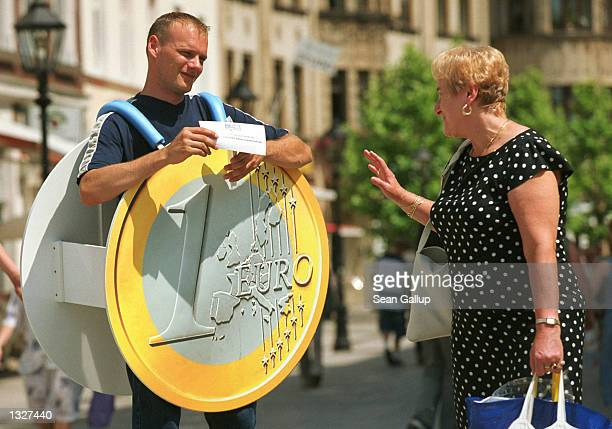 An employee with a traveling information tent to promote the Euro Europe''s new currency hands out promotional brochures June 27 2001 in Zwickau...