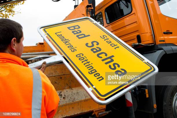 An employee with the county street building authority holds up a town sign written with 'City Bad Sachsa County Goettingen' inBad Sachsa Germany 31...
