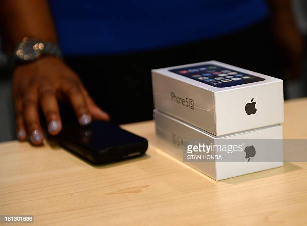 An employee with two Apple iPhone 5 in their boxes at a sale counter in the Apple Store on Fifth Avenue September 20 2013 in New York Some people...