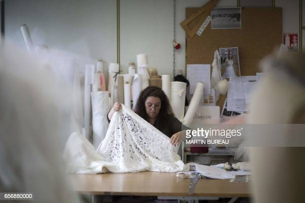 An employee work on a dress on March 21 2017 at the production workshops and offices of the Cymbeline Wedding Dresses house in Avon in the southeast...