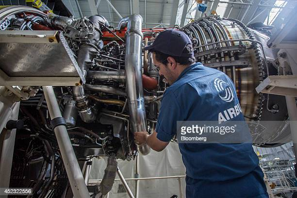 An employee work on a Rolls Royce Trent 900 aircraft engine manufactured by Rolls Royce Holdings Plc as it sits on the Airbus A380 aircraft assembly...