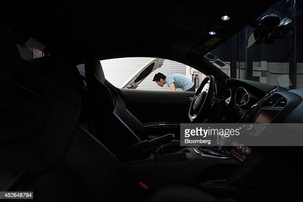 An employee working on a customized Bayerische Motoren Werke AG 1 Series 118d vehicle is seen through the window of a customized Volkswagen AG Audi...