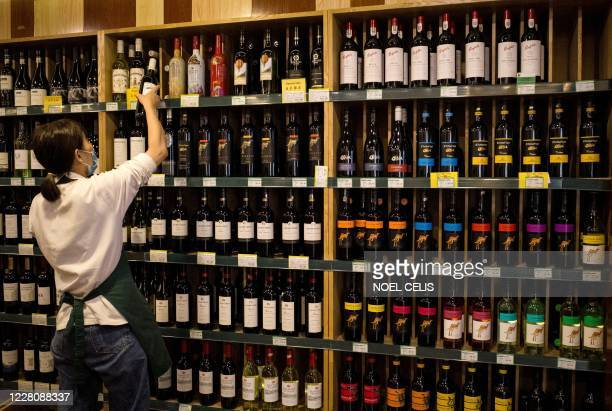 An employee works as Australianmade wine are seen for sale at a store in Beijing on August 18 2020 China on August 18 ramped up tensions with...