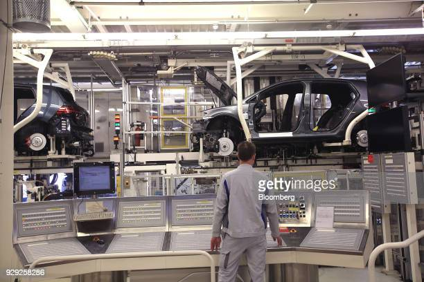 An employee works at a control panel as Volkswagen AG Golf automobiles move along the powertrain assembly line at the VW factory in Wolfsburg Germany...