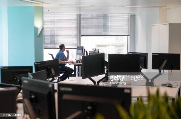 An employee works at a desk at Cushman & Wakefield Plc's offices during the first phase of the reoccupation of their headquarters in London, U.K., on...