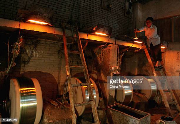 An employee works at a fiberglass factory March 16 2005 in Chengdu Sichuan Province China Premier Wen Jiabao has specifically targeted the widening...