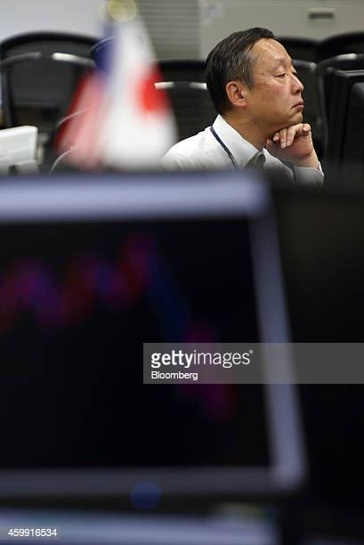 An employee works at a foreign exchange brokerage in Tokyo Japan on Thursday Dec 4 2014 Japanese stocks rose for a fifth day with the Topix index...