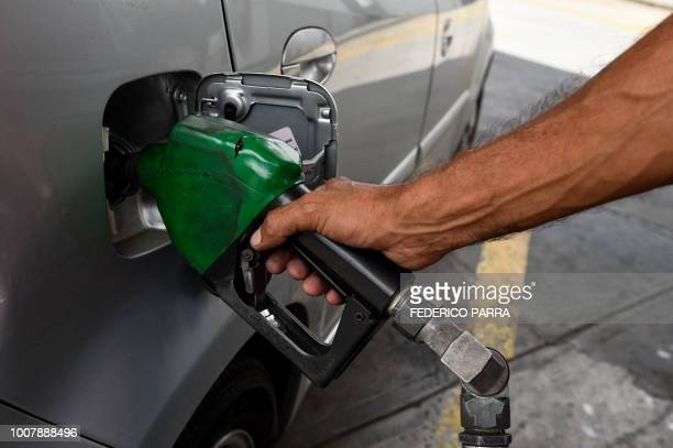 An employee works at a gas station in Caracas on July 30 2018 Venezuelan President Nicolas Maduro announced fuel price regulations for the cheapest...