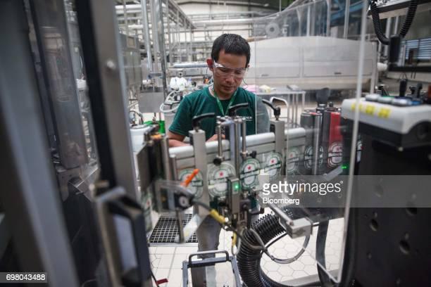 An employee works at a labeling machine in the bottling plant at the Heineken NV brewery in Yangon Myanmar on June 15 2017 Heineken is seeking to...