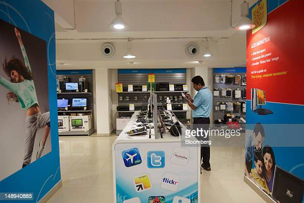 An employee works at a Reliance Digital store a subsidiary of Reliance Industries Ltd in Mumbai India on Friday July 20 2012 Reliance Industries Ltd...