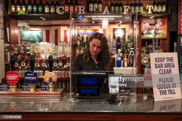 An employee works at a till behind a perspex screen at The Moon Under Water pub, operated by J D Wetherspoon Plc, on Leicester Square in London,...