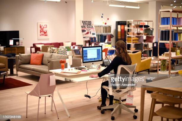 An employee works at her computer in a home and office furniture and accessory store in Santa Fe New Mexico