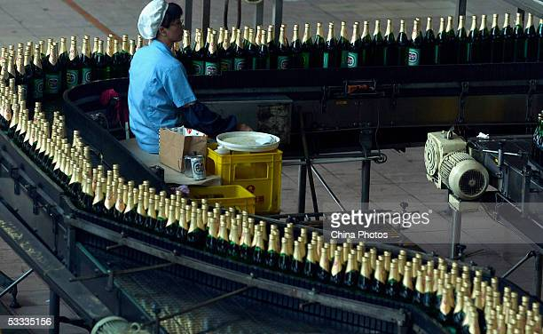 An employee works at the beer production line in Guangzhou Zhujiang Beer Group Company factory on August 6 2005 in Guangzhou of Guangdong Province...