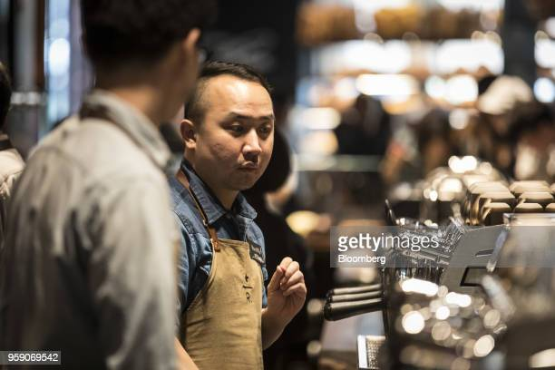 An employee works behind a counter inside the Starbucks Corp Reserve Roastery store in Shanghai China on Friday May 11 2018 Starbucksis laying out...
