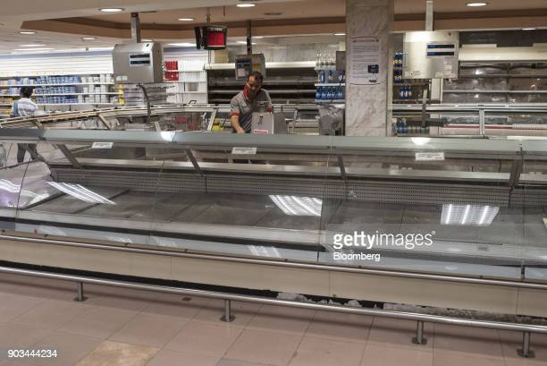 An employee works behind an empty counter in the deli section of a grocery store in Caracas Venezuela on Tuesday Jan 9 2018 Hordes of desperate...