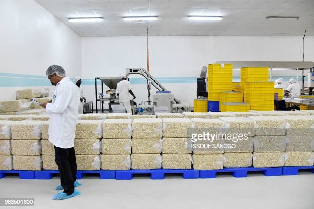 An employee works by bags of processed cashew nuts at a cashew nuts processing factory in the central Ivorian city of Bouake on May 24, 2018.